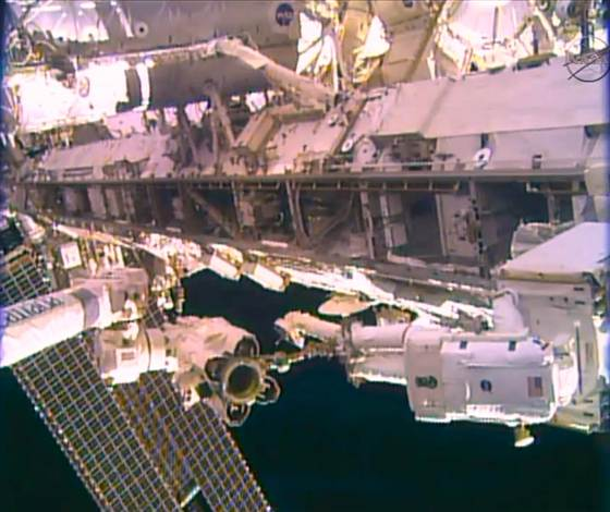 In the foreground, NASA astronaut Rick Mastracchio helps guide the refrigerator-sized, 780-pound coolant pump module to its storage spot while standing on the end of the Initernational Space Station's robotic arm.