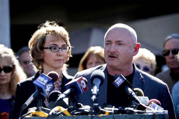 Former Congresswoman Gabrielle Giffords listens as her husband, retired astronaut Mark Kelly, speaks at a March news conference in Tucson, Ariz.