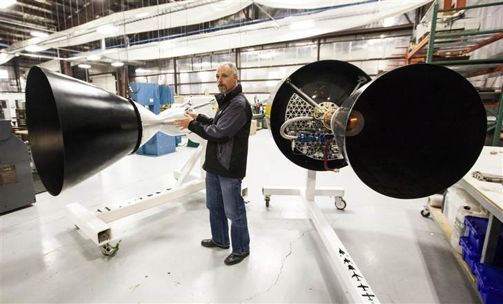 Propusion engineer Robyn Ringuette shows off models of the NewtonTwo and NewtonOne engines at a Virgin Galactic production facility in Mojave, Calif.