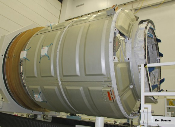 Cygnus pressurized cargo module – side view – during prelaunch processing by Orbital Sciences at NASA Wallops, VA. Docking mechanism to ISS at right.